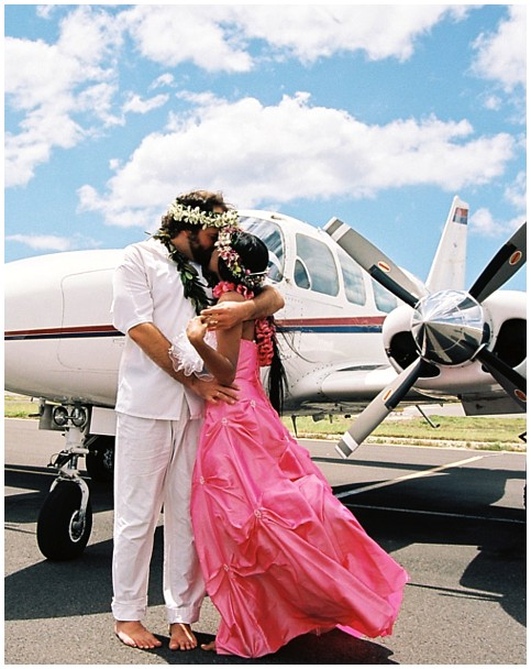 paul and dewi embrace by a airplane wearing haku leis