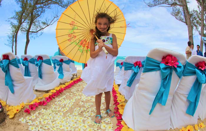 little gril holding umbrella at beach wedding
