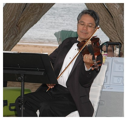 playing the violin at a beach wedding in hawaii