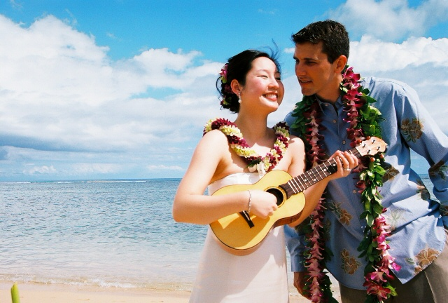 bride playing the ukulele for her groom in Hawaii