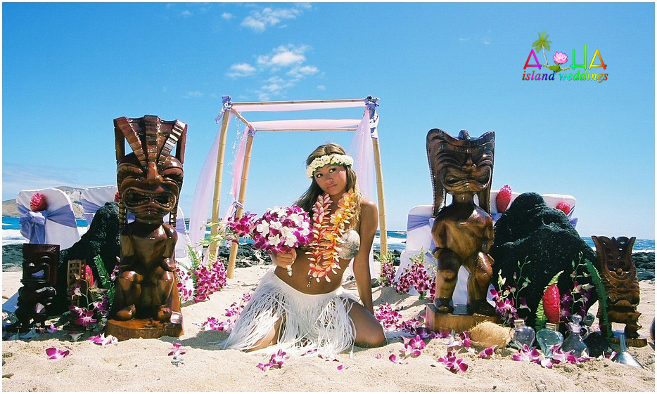 Hawaiian hula girl poses next to the tiki gods Lono and Kane represent Happy and Lucky at wedding in Hawaii