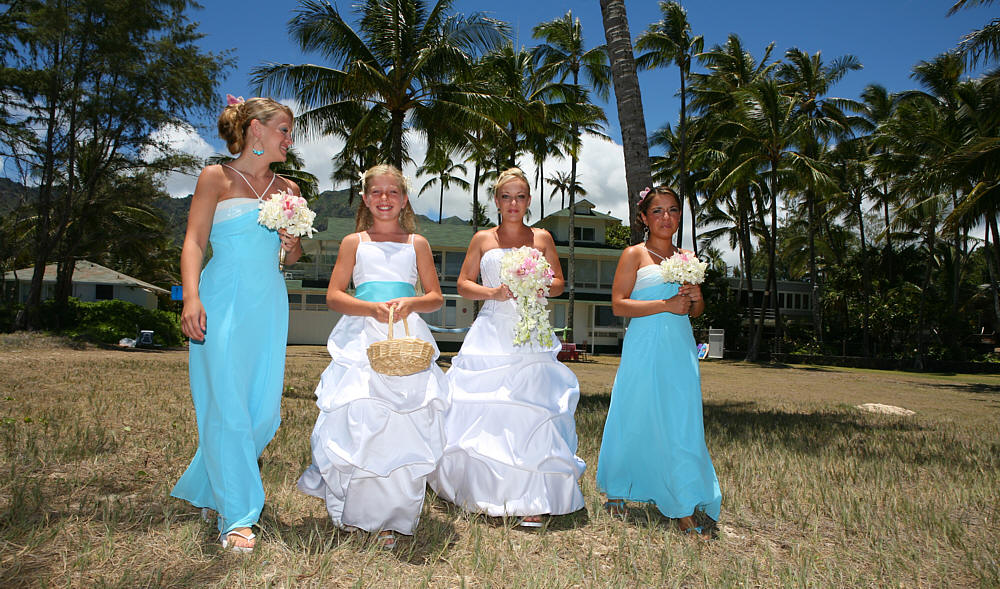 angela and her bridesmaids walking to their wedding on the beach in AHwaii