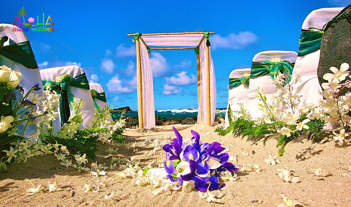 Blue iris flower bouquet lays on the sand with white orchids for this makapuu beach wedding