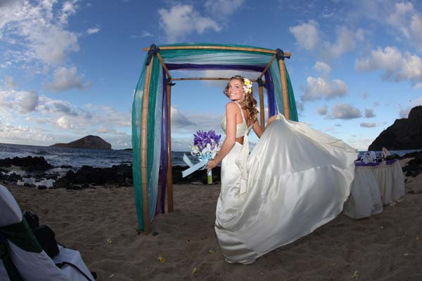 Jenna posing after her Hawaiian wedding close to sunset on the beach under her gazebo