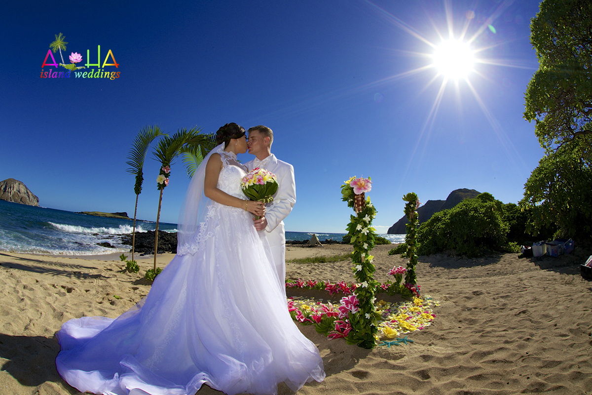 Kiss after the wedding with the sun shinning through on this beaitoful Hawaii beach ceremony holding a multi color plumeria bouquet