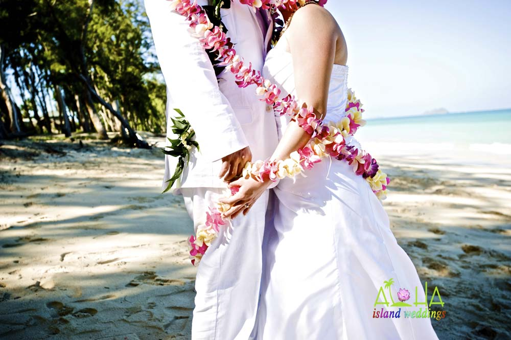 tied with the love of flower leis around them at the Hawaiian wedding