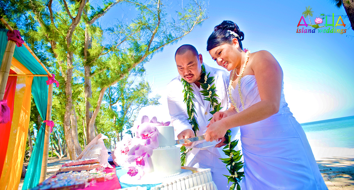 cutting the cake on the beach by the gazebo