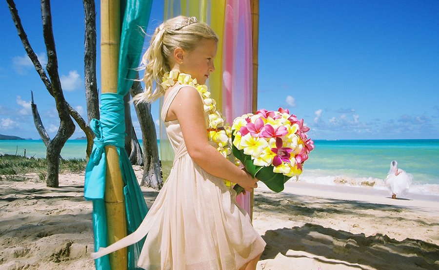 bride holding plumeria bouquet while bride is on the beach