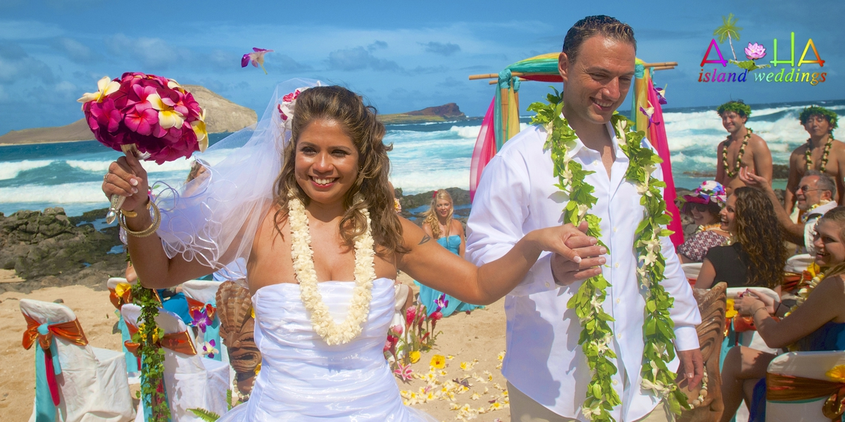 the couple dances down the aisle way with her pink and yelow bouquet and maile lei