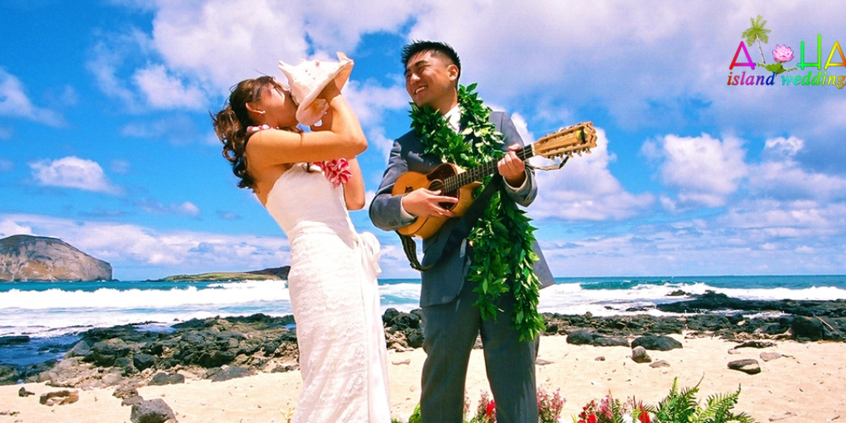 The groom plays the ukulele for his bride as she plays the conch shell  in a flower circle