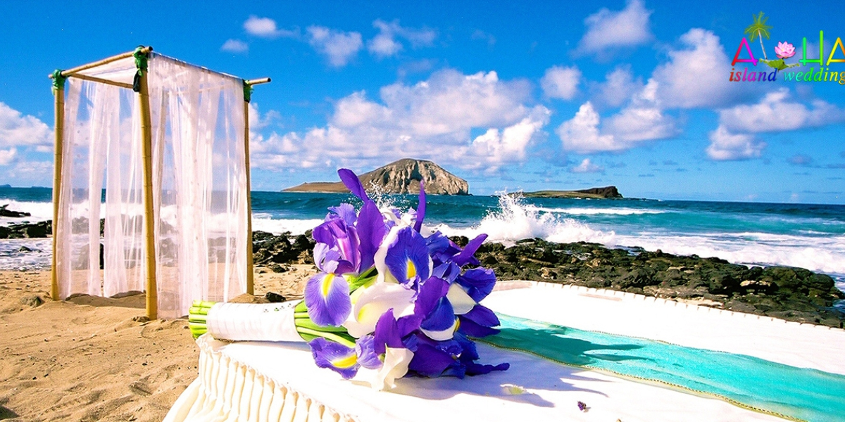 All white wedding arch with a flower bouquet of white and blue on the table while the waves crash on the rocks