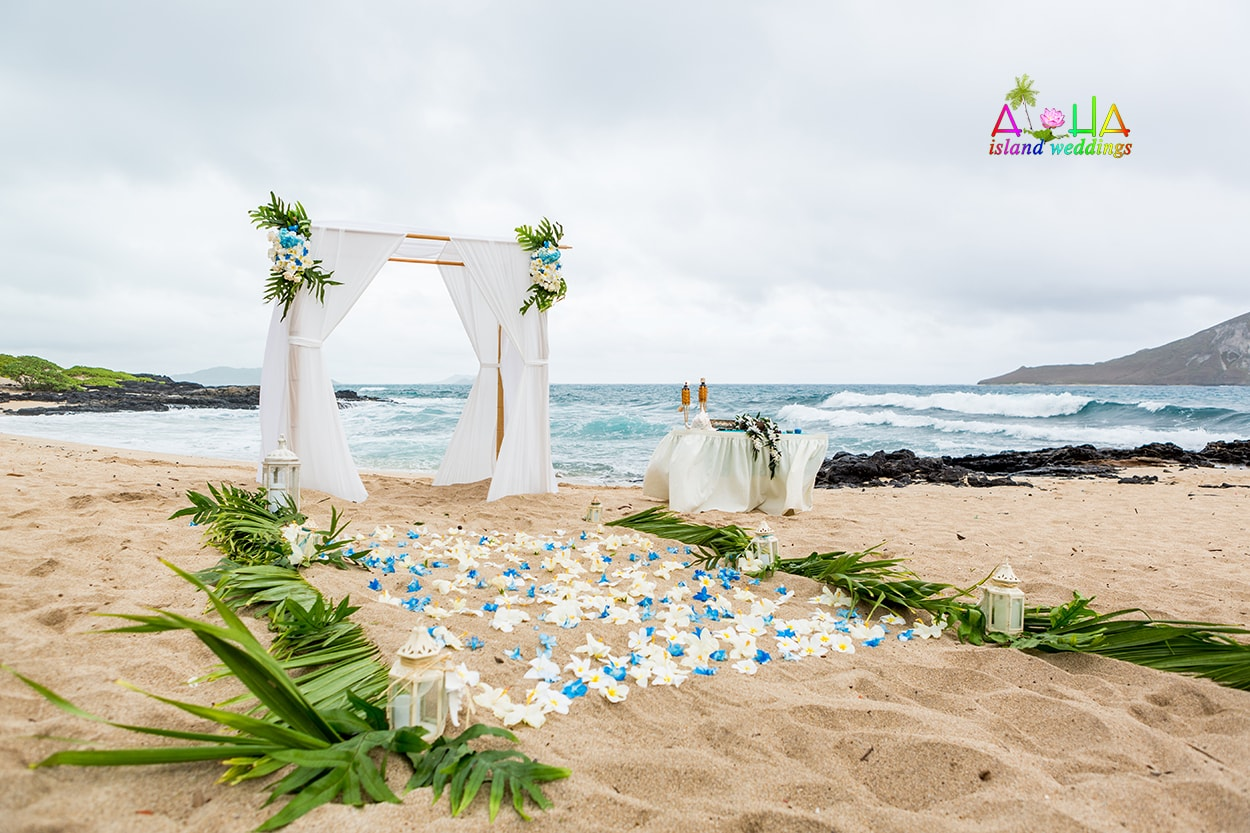 white and ligth blue flowers on the sand with candels and palms with a pure white wedding arch for the Hawaii beach wedding