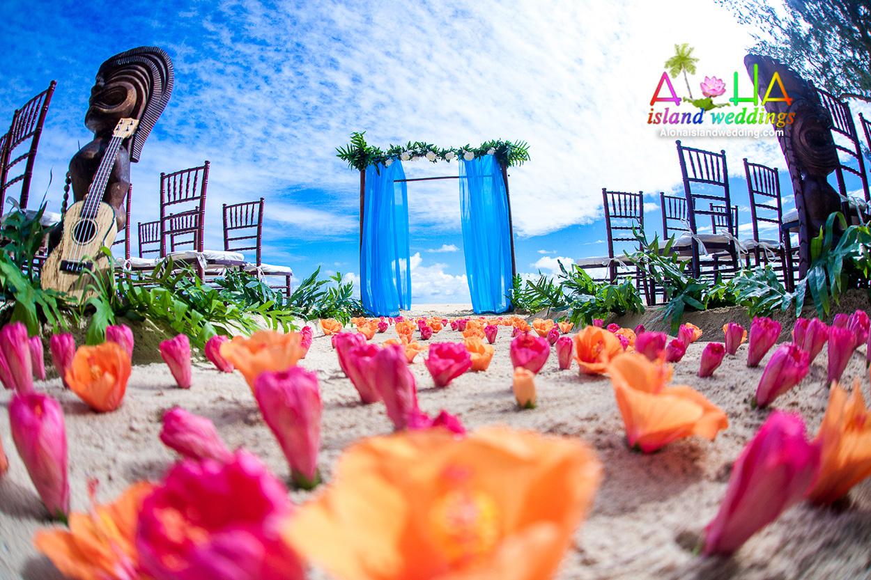 chiavari chairs with bamboo archway wedding in Hawaii with tiki men standing guard with orange and pink hibiscus