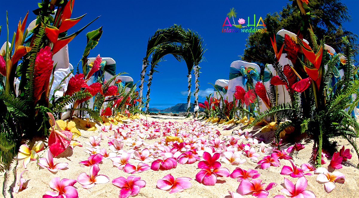 Palm on the sand archway bamboo wrapped with white and green fern with lots of Hawaiian florals of red and yellow