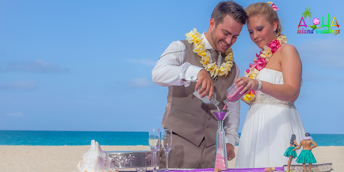 pouring pink and white sand at their hawaii beach wedding