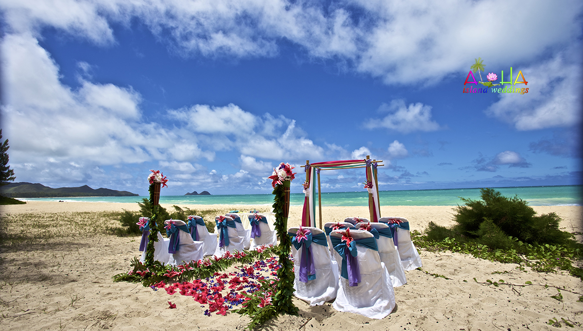 Tiki torches with palms on the grassy beach with pirple blue and pink themed beach wedding