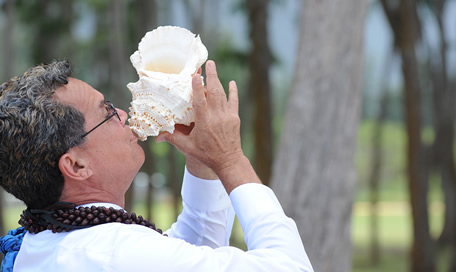 minister Kimo taylow blowing the conch at a wedding