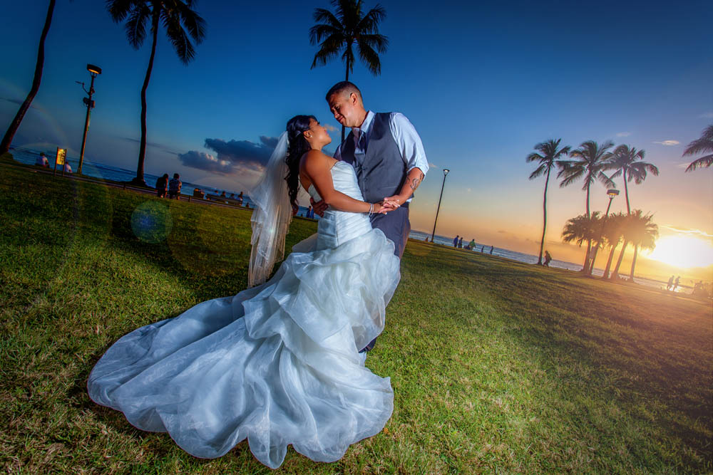 dipping his bride while the sun is going down at the beach of Hale Koa fort derussy