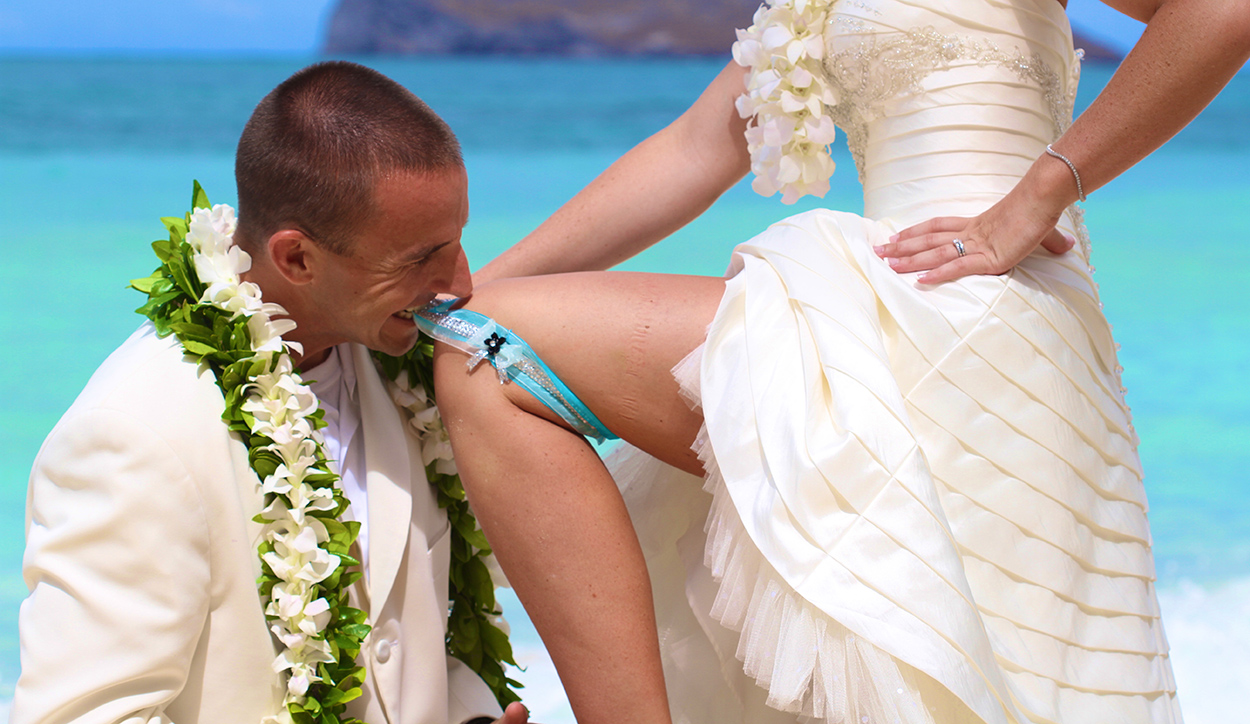 pulling on the garter belt with his teeth on the beach
