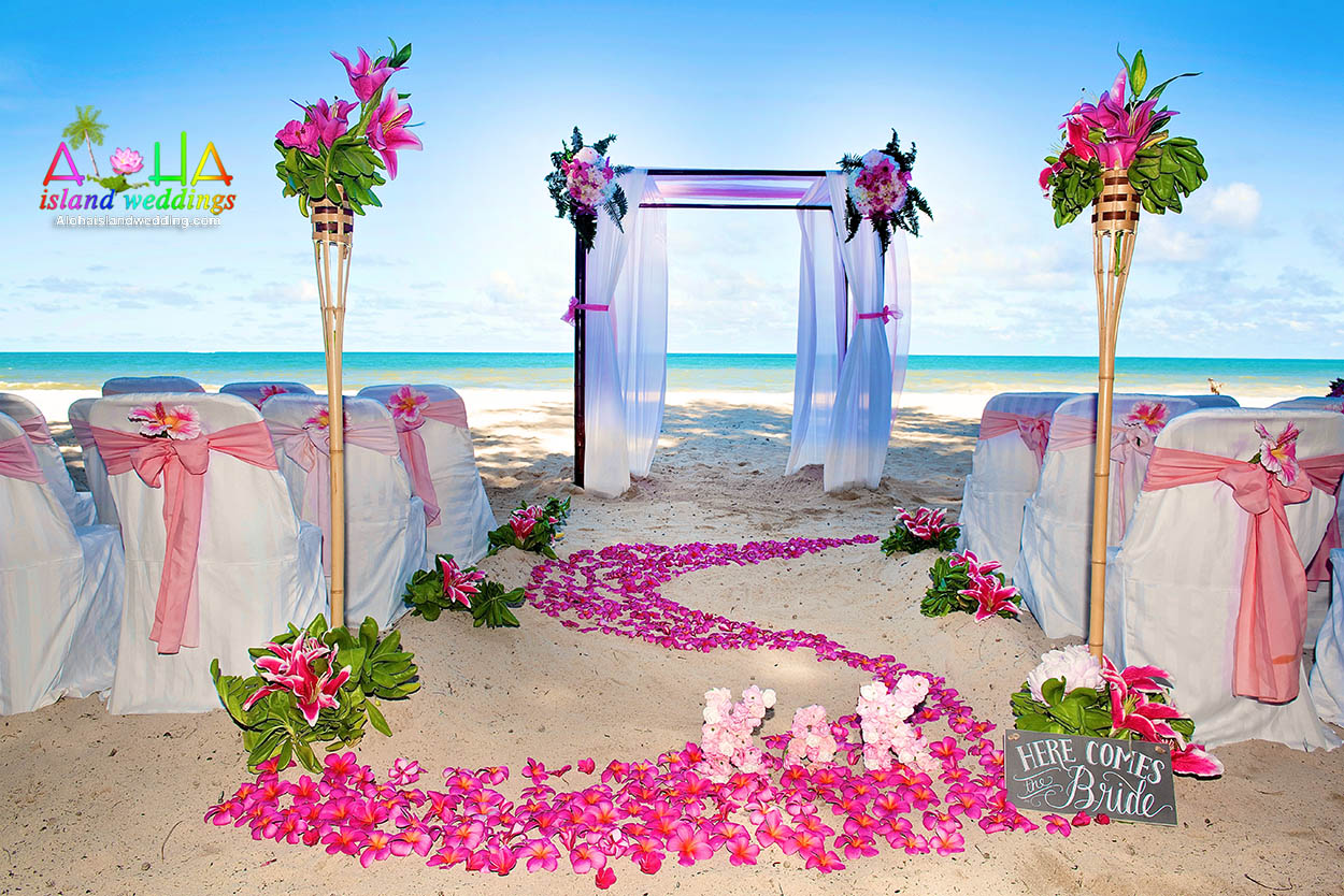 two tiki bamboo torches with hot and dark pink flowers and a swirl of pink plumerias line the aisle way up to this wedding deisgn on Oahu