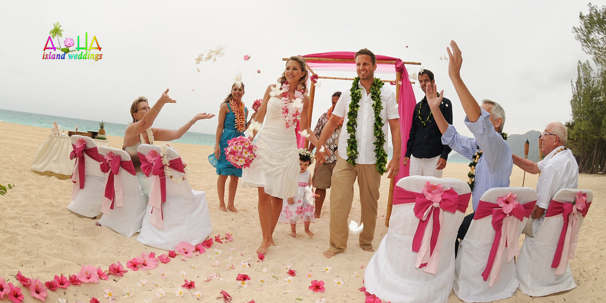 pink flowers are thown at the wedding couple as they walk down the aisle way