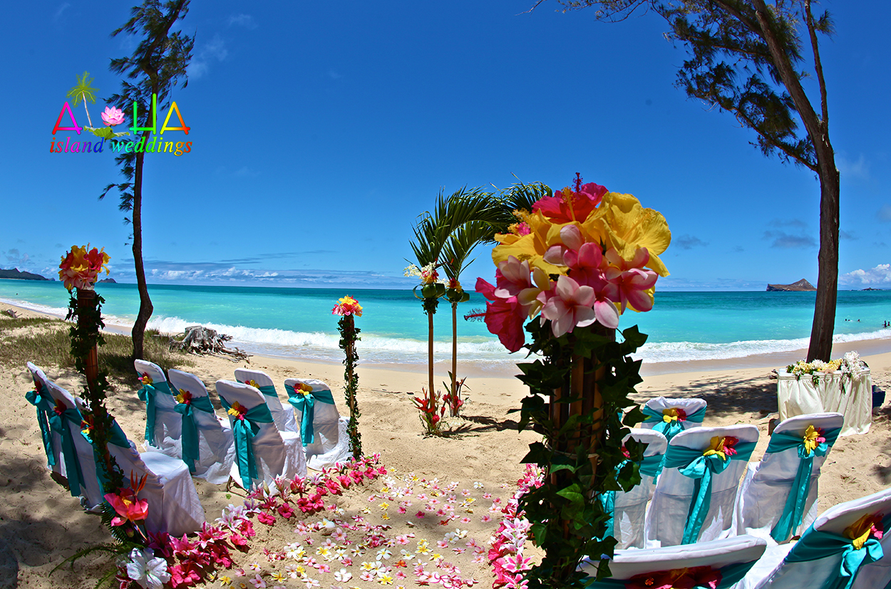 bright yellow and light and dark pink plumerias on the tiki torch at a beach wedding