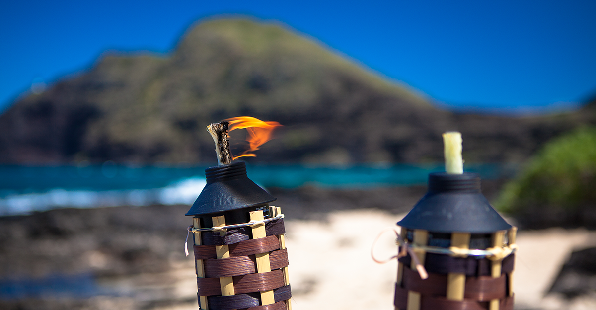 one fire torch lite awaiting the bride and groom to ignite the other one in Hawaii on the beach