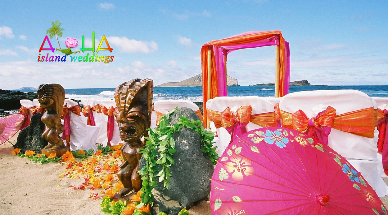 Orange and pink Tiki themed Hawaii beach wedding with maile leaves and multi orange and yellow flowers on the sand