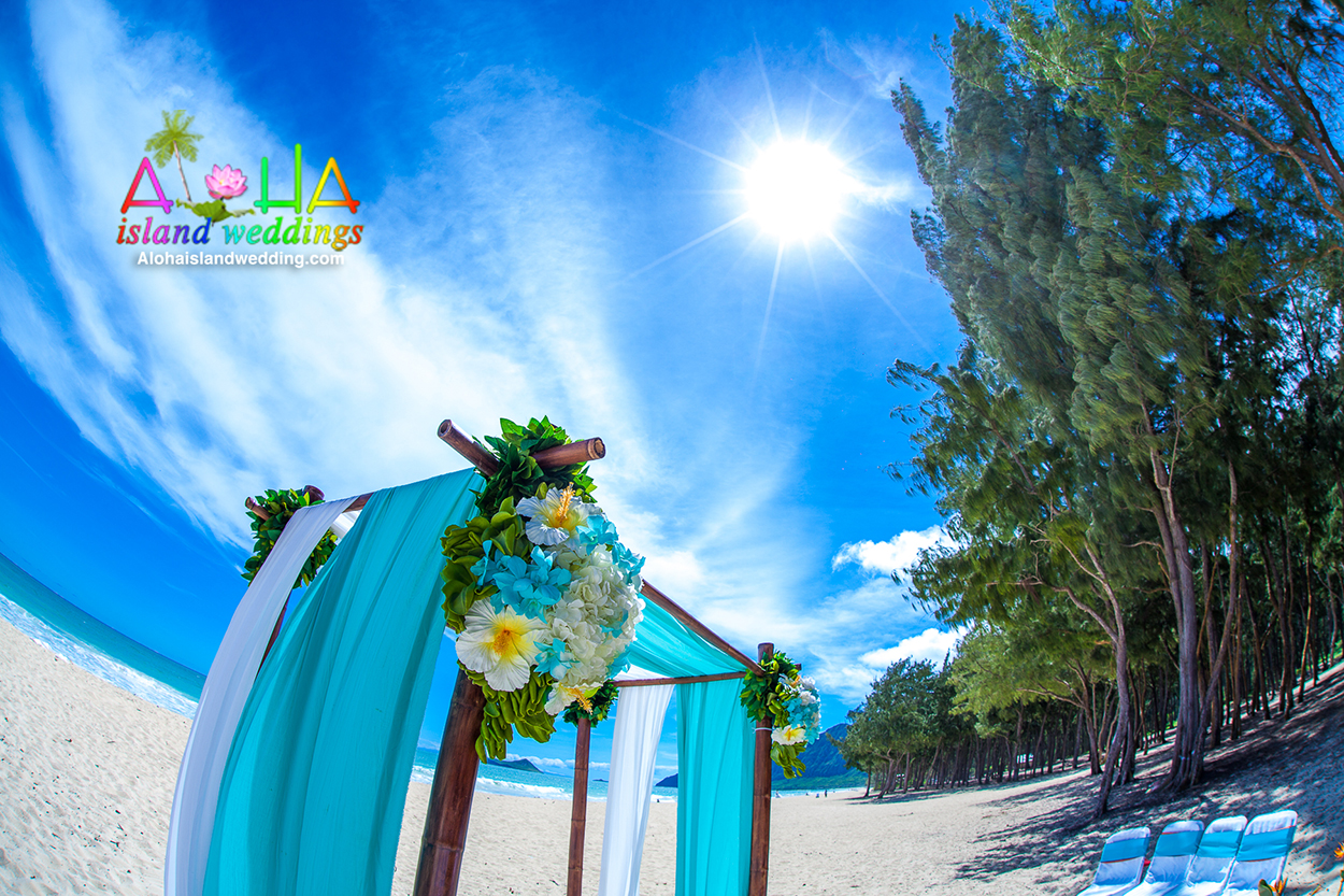sun shinning down on this turquoise beach themed arch in Hawaii with fern greenery wrapped around the bamboo arch , trees and mountain in the background