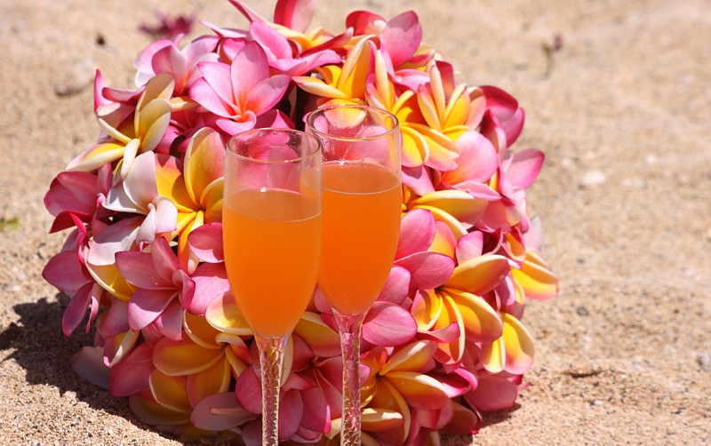 guava drink in champagne glasses with plumeria bouquet