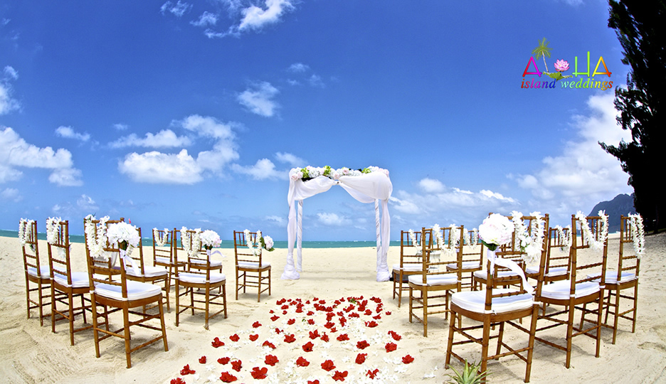 White orchids with red hibiscus and wooden chairs with a beach arch create this setting for a Hawaii beach wedding
