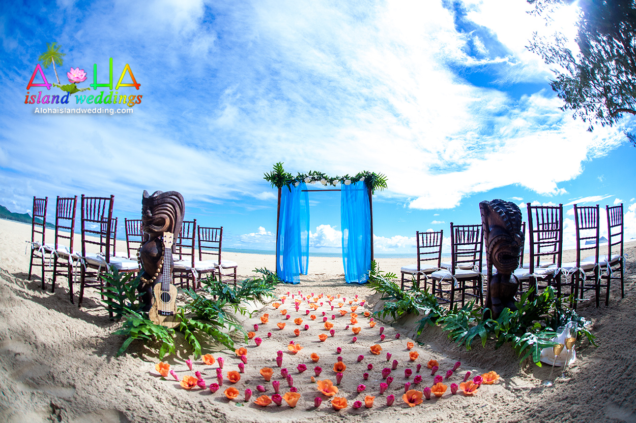 Wooden chiavari chairs at this beach wedding with Hawaiian Tiki men
